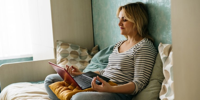 A middle-aged woman sitting in a yoga pose at home on a sofa in casual closes  with laptop and meditating