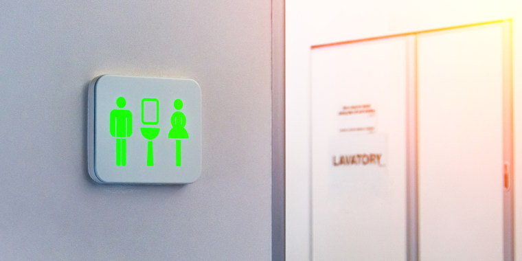 Not occupied toilet sign is marked in green, against the background is a door from the wc inside the plane.