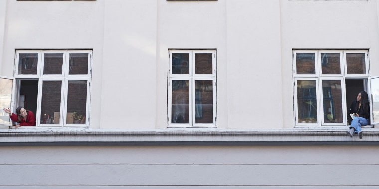 Young female neighbors talking from apartment windows