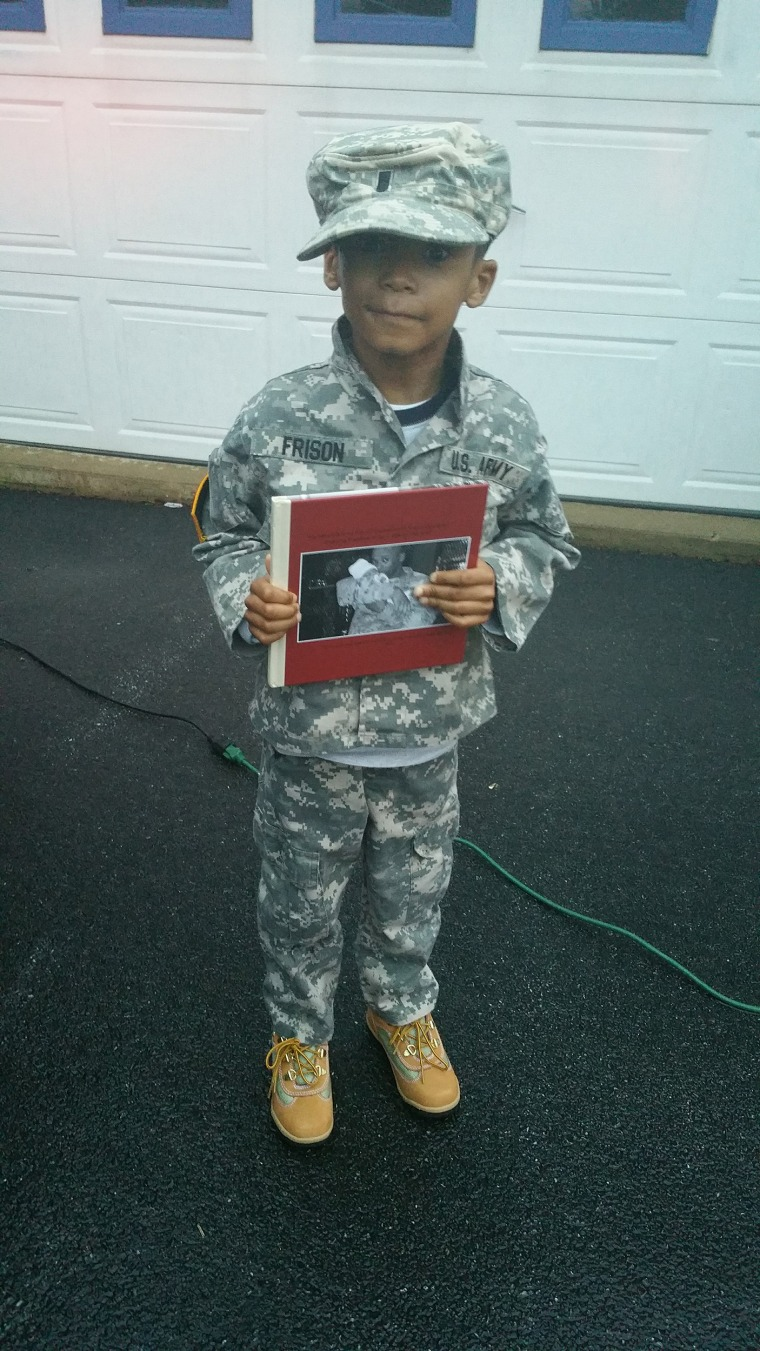 Chris Frison holds a photo of his dad, Demetrius Frison, a first lieutenant in the U.S. Army who died in an explosion in Afghanistan in 2011 when Chris was a baby.