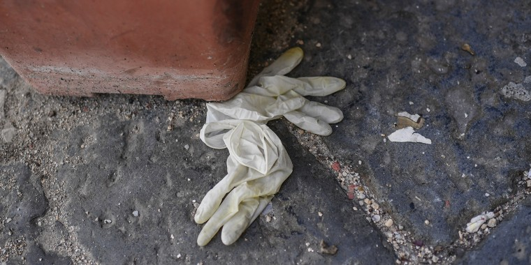 Worn-out protection gloves lie thrown away on the street, in