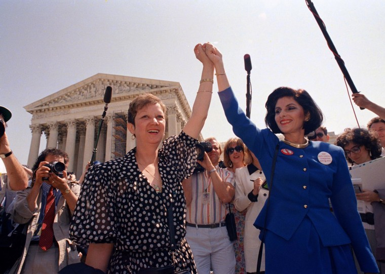 """Image: Norma McCorvey, also known as \""""Jane Roe\"""" in the 1973 court case Roe v. Wade, holds hands with her attorney, Gloria Allred, as they leave the Supreme Court in 1989."""