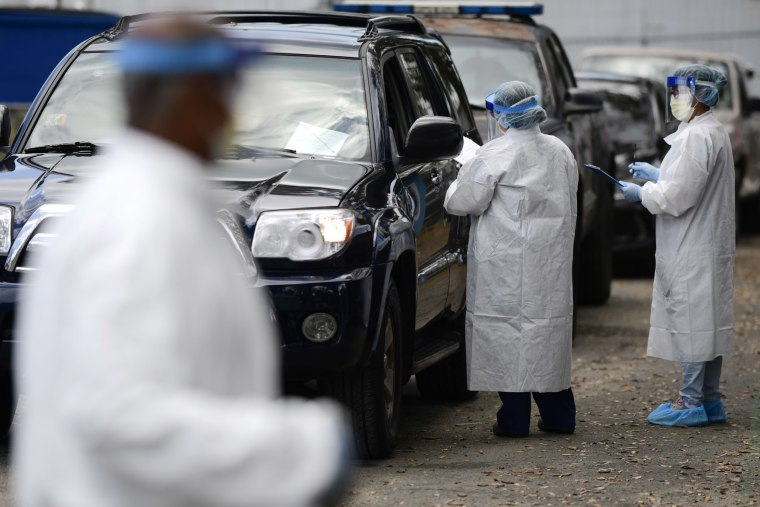 Image: Health Department nurses collect samples from doctors, paramedics and police officers at a drive-thru checkpoint to perform molecular tests that detect the new coronavirus virus, in San Juan, Puerto Rico