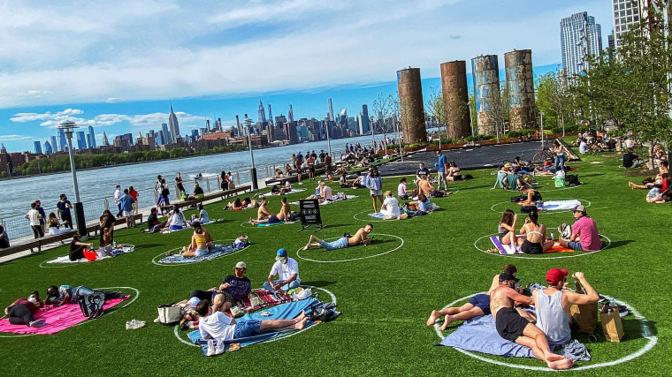 Image: People try to keep social distance as they enjoy a warm day during the outbreak of the coronavirus disease (COVID-19) at Domino Park in Brooklyn, New York