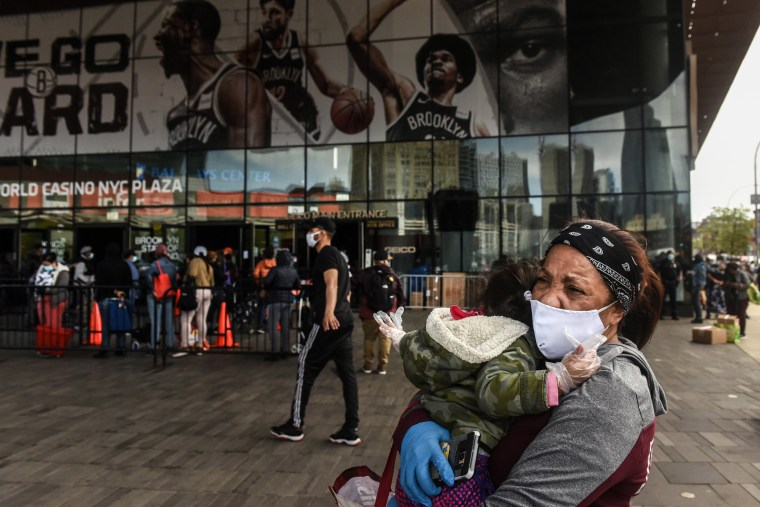 Image: Santa Arias holds her grand daughter as she decides whether to wait on a long line for a food bank donation at the Barclays Center on May 15, 2020 in the Brooklyn borough in New York City.