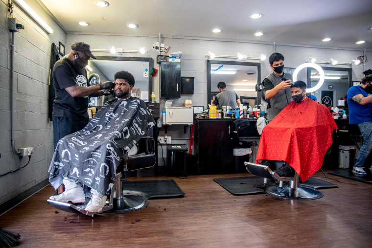 Image: Two men get their hair cut at a barbershop in Austin, Texas on May 8, 2020.