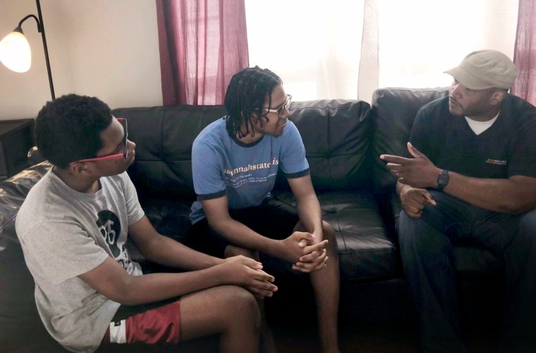 Image: Carlton Riddick, right, finds it frustrating that it is necessary to have talks with sons Justin, left, and Josiah about surviving targeted attacks.