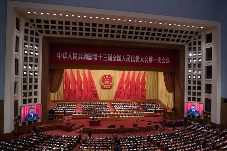 Image: Chinese President Xi Jinping (at podium) delivering a speech during the closing session of the National People's Congress at the Great Hall of the People in Beijing