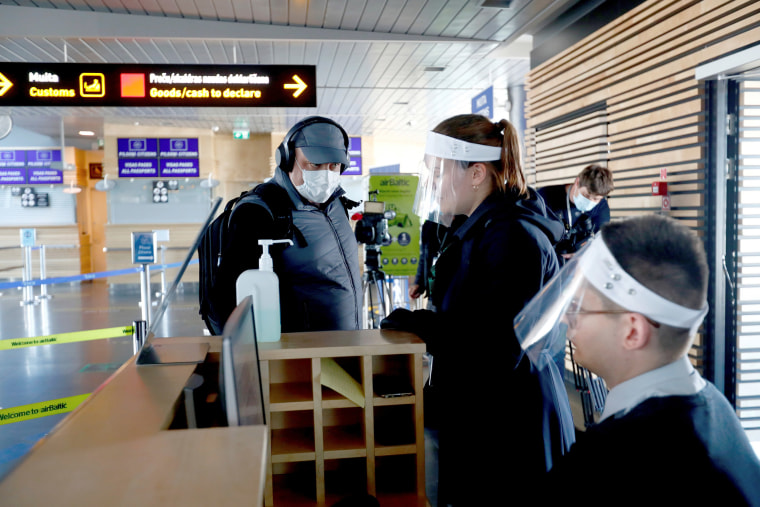Image: A man boards on a plane as flights resume during the coronavirus disease (COVID-19) outbreak in Riga international airport, Latvia