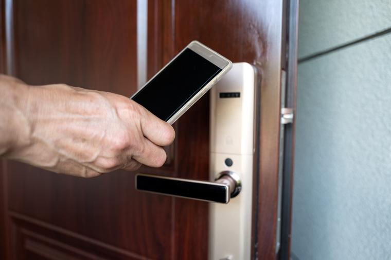 Human hand uses mobile phone to sense room door