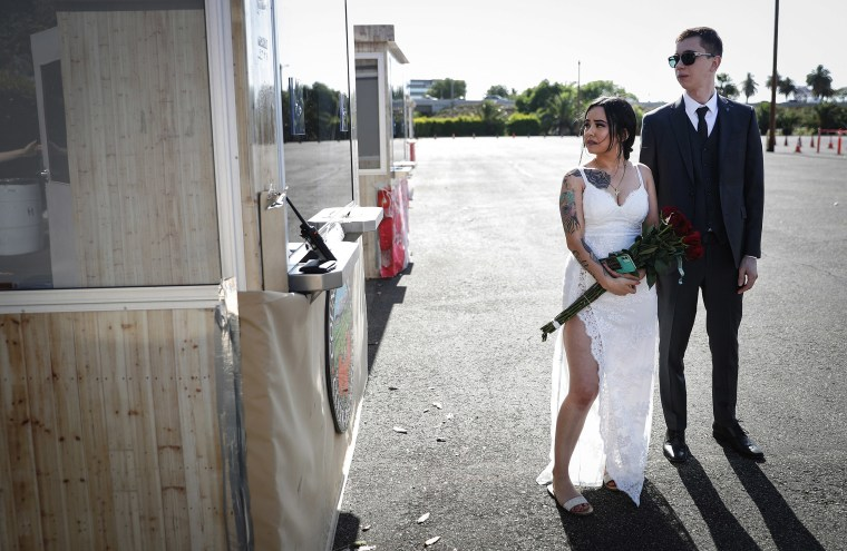 Image: A couple wait to exchange marriage vows at one of six pop-up socially distanced marriage booths in the parking lot of the Honda Center amid the coronavirus pandemic on May 19, 2020 in Anaheim, California.