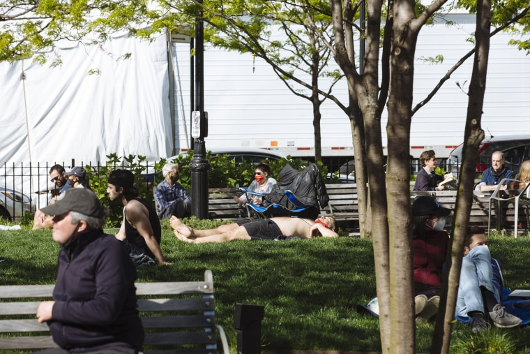 Image: People sunbathe and sit in St. Vincent's Triangle park in front of a refrigerated tractor trailer being used as an overflow Morgue at Lennox Health Greenwich Village Hospital in New York City