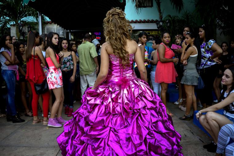 Girls watch Amanda Teresa Betancourt during her quinceanera photo shoot with EstudiosMayer in Havana, Cuba on Dec. 13, 2015.