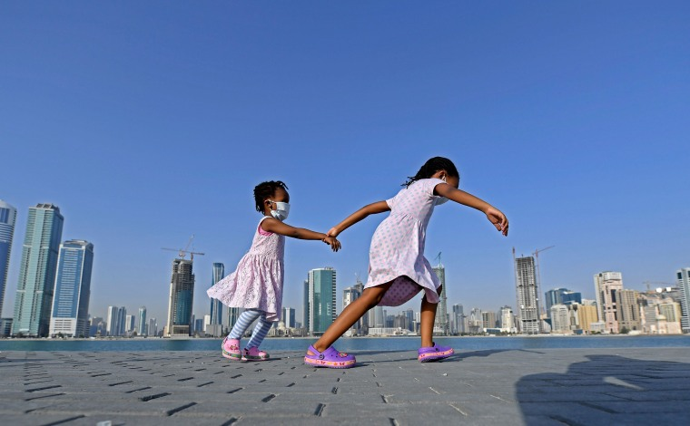 Image: A girl, wearing a face mask due to the COVID-19 coronavirus pandemic, runs with another child by the waterfront at al-Mamzar district in Dubai