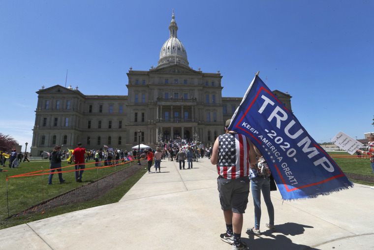 Protesters carry a Trump 2020 flag at the State Capitol during a rally in Lansing, Mich., on May 20, 2020, where barbers and hair stylists protested the state's stay-at-home orders.