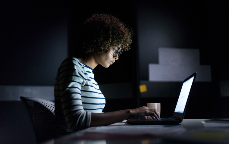 Concentrated woman working late hours with her laptop