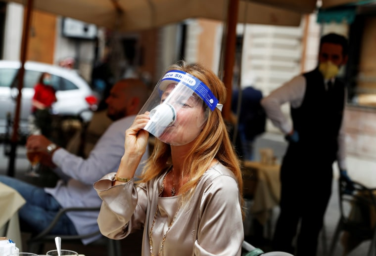 A woman wearing a face shield enjoys a coffee in Rome as Italy eases lockdown measures on May 18.