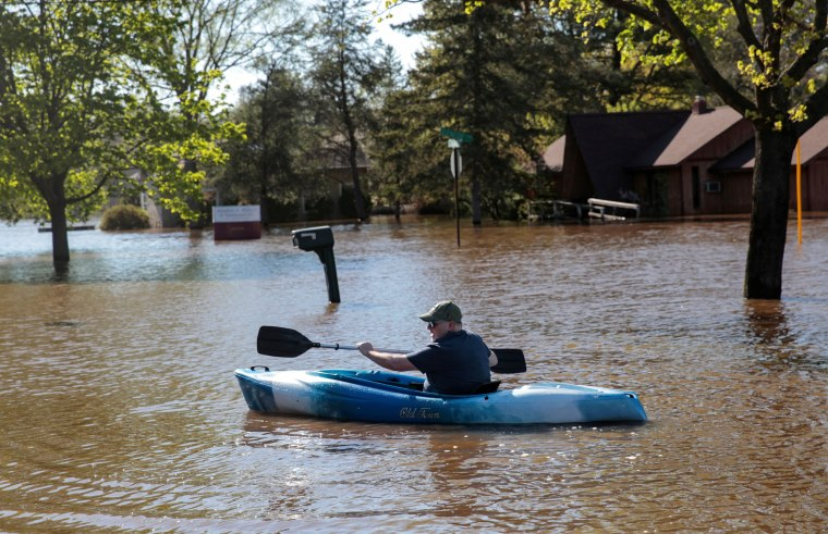 Image: Resident Joe Ryan paddles a kayak to check on his home in a flooded neighborhood along the Tittabawassee River, after the two dam failures in Midland, Michigan
