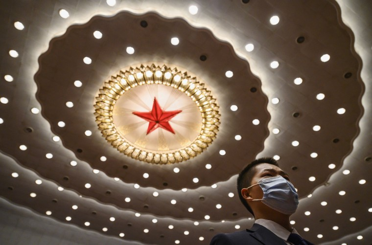 Image: A Chinese security guard wears a protective mask as he stands after the opening of the National People's Congress