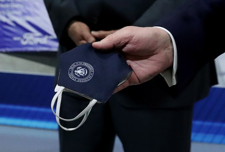 Image: President Donald Trump holds a protective face mask with a presidential seal on it that he said he had been wearing earlier in his tour at the Ford Rawsonville Components Plant