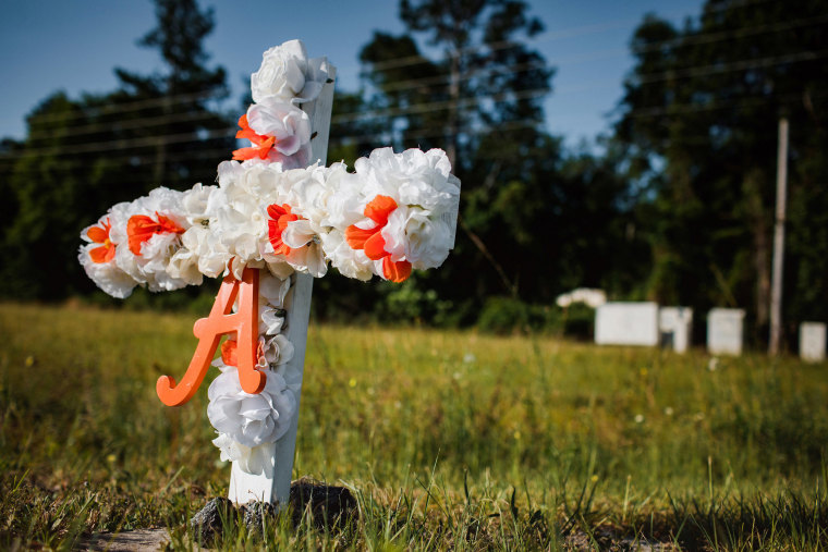 """Image: A white and orange cross with an \""""A\"""" on it stands stuck in the ground along highway 17 at the entrance of the Satilla Shores neighbourhood where Ahmaud Arbery, an unarmed young black man, was shot after being chased by a white former law enforcemen"""