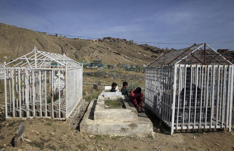 Image: Afghan children sit on a grave on the outskirts of Kabul, Afghanistan