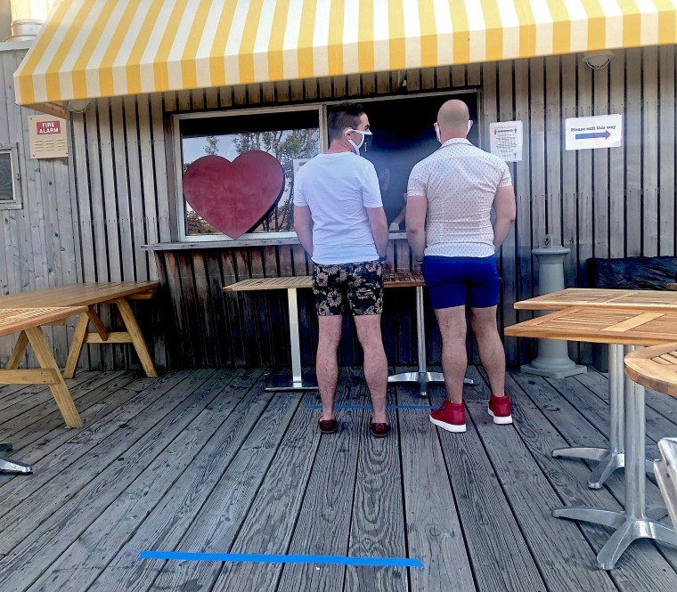 Two vacationers wear masks as they visit the Cantine in Fire Island Pines.