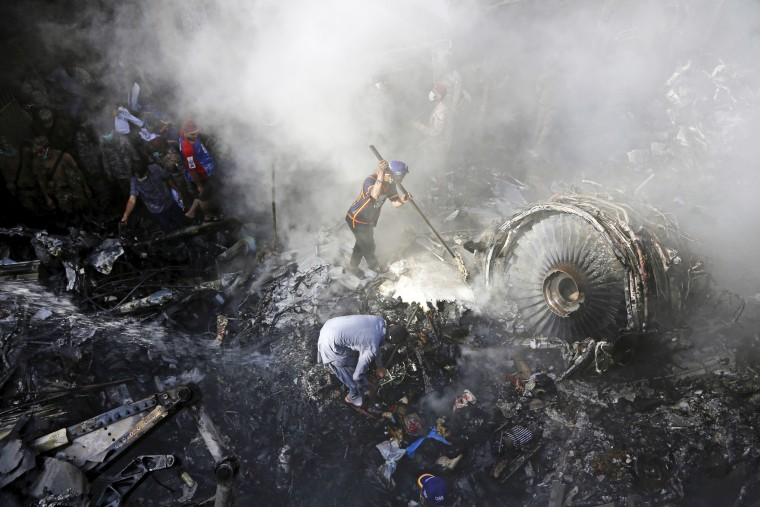 Volunteers look for survivors after a plane crashed in a residential area of Karachi, Pakistan, on May 22, 2020.
