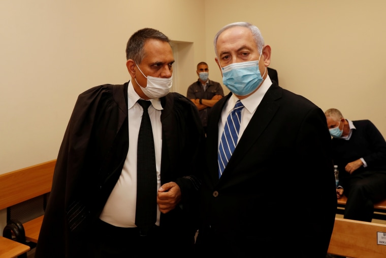Image: Israeli Prime Minister Benjamin Netanyahu, wearing a mask, stands inside the courtroom as his corruption trial opens at the Jerusalem District Court