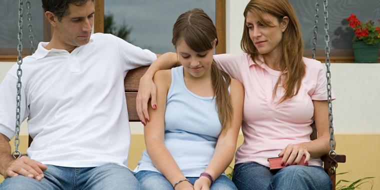 Parents comforting daughter