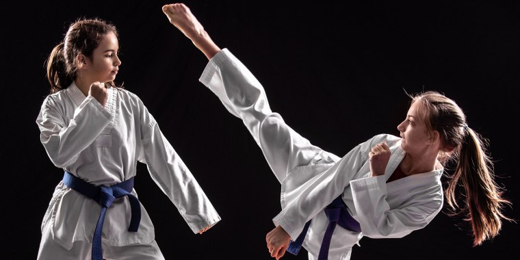 Two girls in taekwondo combat