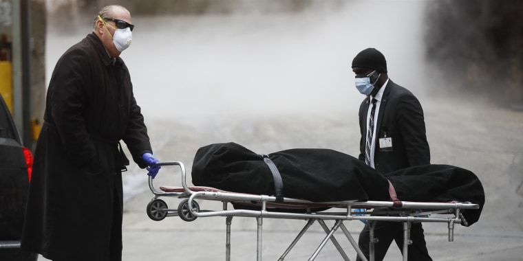 A funeral director wears personal protective equipment due to COVID-19 concerns while collecting a body at the Brooklyn Hospital Center in Brooklyn, New York, on April 9.