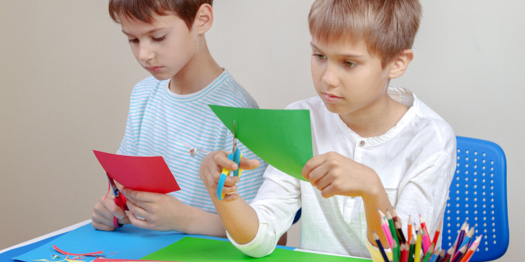 Friends Cutting Colorful Papers In Classroom