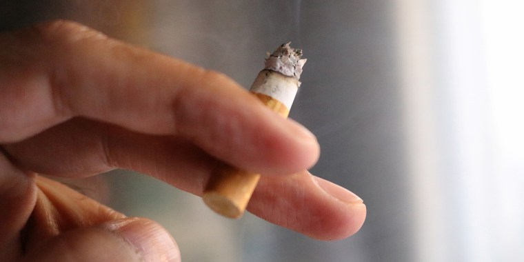 Cropped Image Of Hand Holding Burning Cigarette