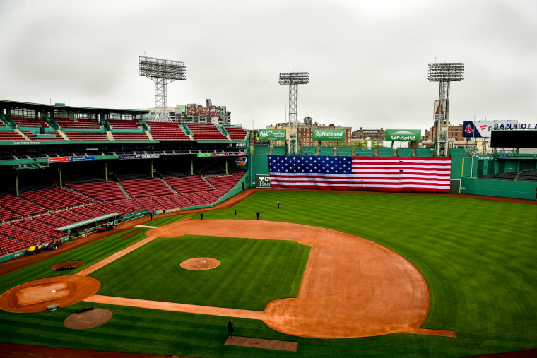Image: An American flag is dropped over the Green Monster inside an empty Fenway Park in Boston on May 25.
