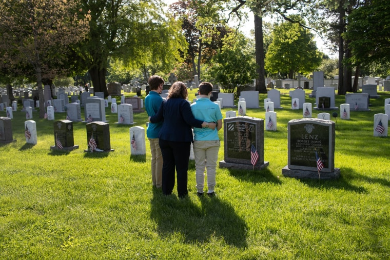 Image: Traci Voelke and her sons, AJ and Benjamin, visit the grave of her husband, U.S. Army Maj. Paul Voelke, at West Point, N.Y., on May 24. Military cemeteries are closed to the public and only open to veterans' families due to coronavirus restrictions