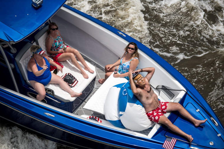 """Image: A boater dressed as President Donald Trump relaxes during a \""""Make America Great Again\"""" parade in Charleston, S.C., on May 24."""