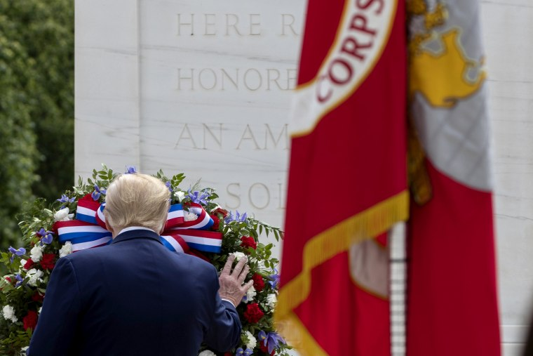 Image: President Donald Trump touches a wreath at the Tomb of the Unknown Soldier at Virginia's Arlington National Cemetery on Memorial Day, May 25.
