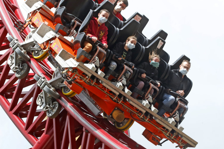 Image: People wearing masks ride a roller coaster at Lagoon Amusement Park in Farmington, Utah, on May 23. Lagoon officials said a new reservation system is in place to help manage social distancing and avoid crowding at the park entrance.