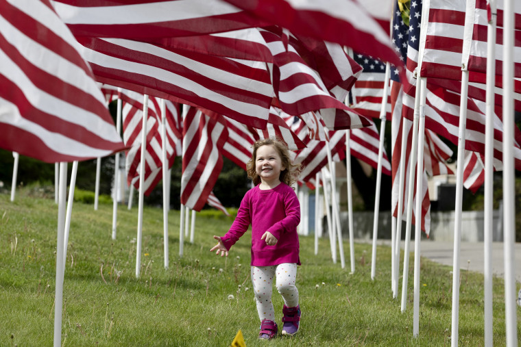 Image: Hazel Roberts walks through a field of flags ahead of Memorial Day in Cohasset, Mass., on May 23, 2020.
