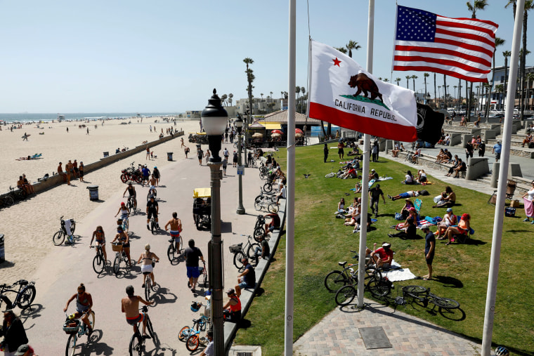 Image: People visit California's Huntington Beach on May 23.