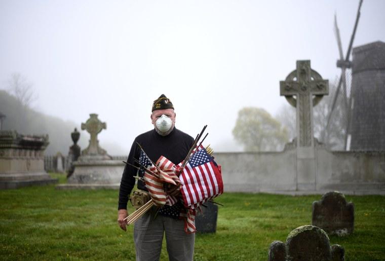Image: Retired Marine Corps Brian Carbine, 78, places American flags at veteran gravesites at the South End Cemetery in East Hampton, N.Y., on May 23. Carbine served in the Vietnam War and Desert Storm.