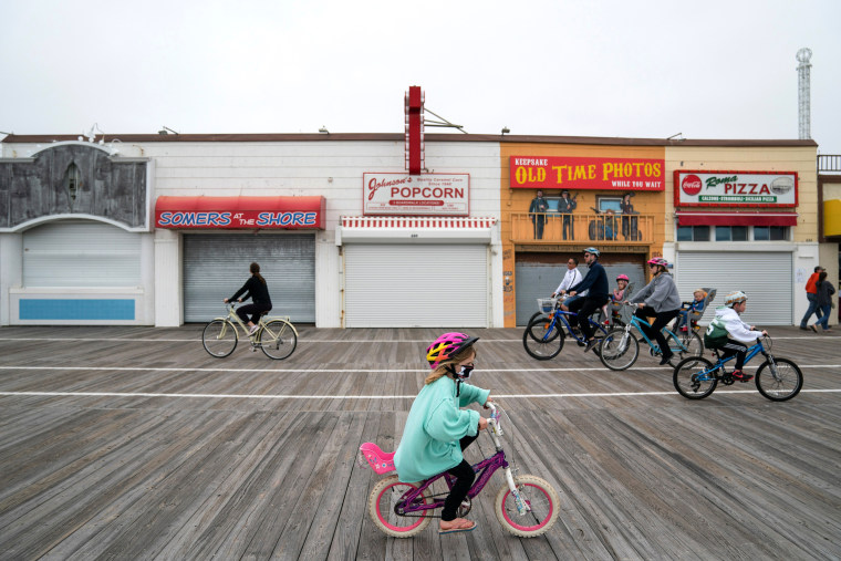 Image: People ride bicycles along the Ocean City boardwalk in N.J. on May 25, 2020.