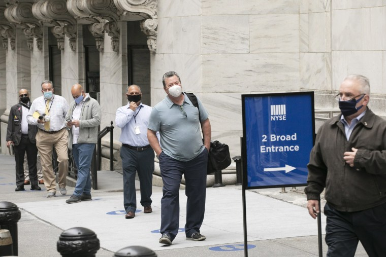 New York Stock Exchange employees wait to enter the building as the trading floor partially reopens on May 26, 2020.