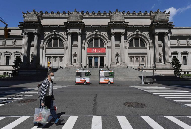 Image: A man wearing a face mask walks past the Metropolitan Museum of Art in New York