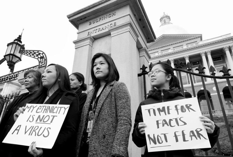 Members of Massachusetts' Asian American Commission stand together during a protest on the steps of the State House in Boston on March 12.