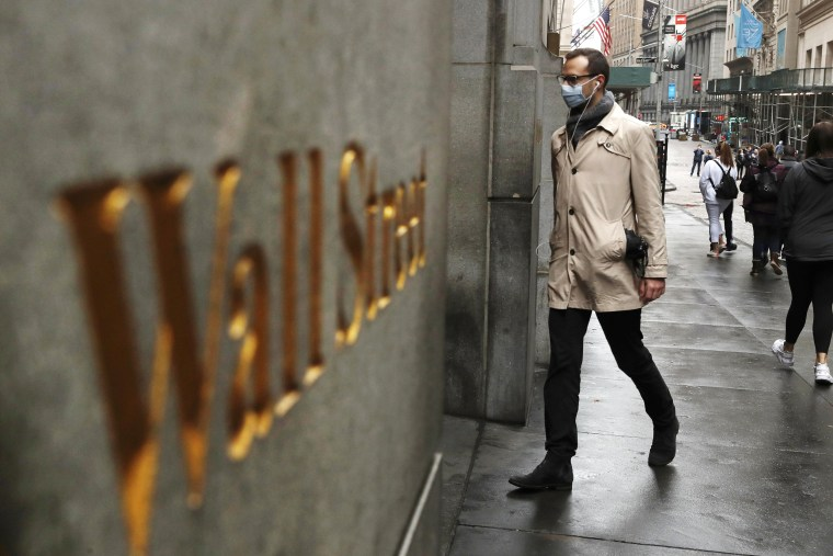 Image: A man wears a protective mask as he walks on Wall Street during the coronavirus outbreak in New York