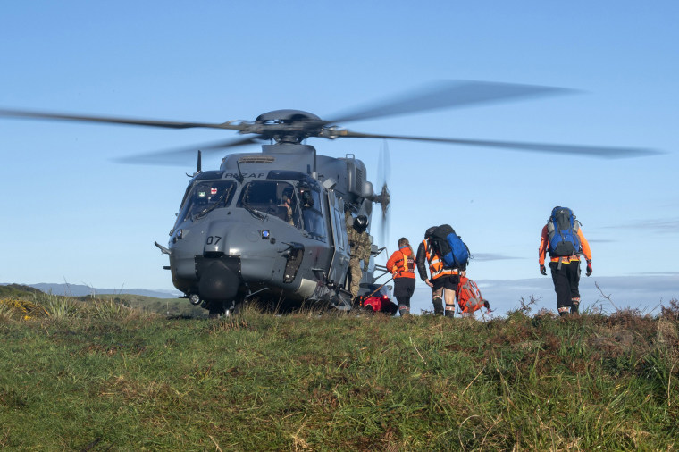 Image: A helicopter waits as search and rescue workers board during a rescue operation to find two missing trampers in the Kahurangi National Park in the South Island of New Zealand