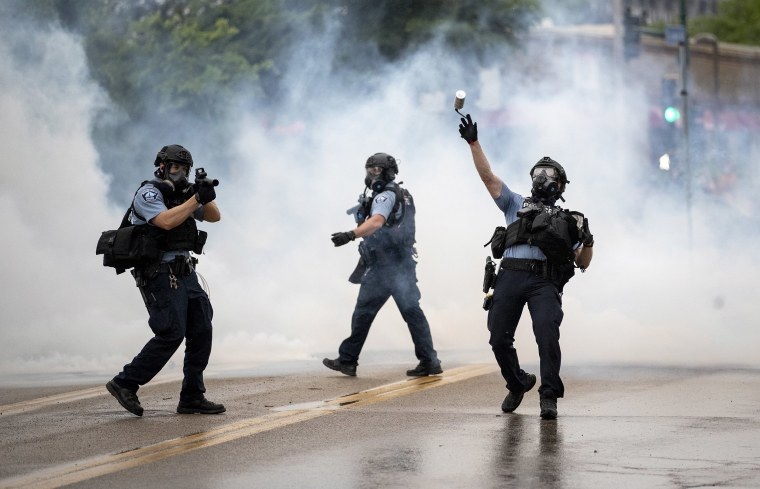 Image: A police officer throws a tear gas canister towards protesters at the Minneapolis 3rd Police Precinct, following a rally for George Floyd