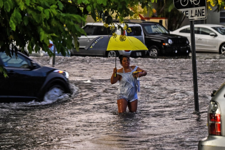 A woman walks through floodwaters during heavy rainfall in Miami on May 26, 2020.